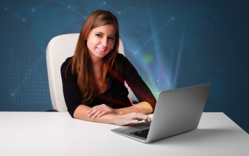 Beautiful young woman sitting at desk and typing on laptop with abstract lights